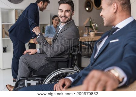 selective focus of smiling disabled businessman and colleagues in office