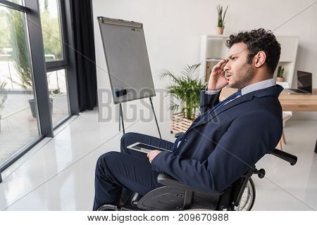 side view of disabled african american businessman with tablet in office