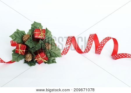 Decoration of crown-shaped parties on white background with red ribbon, green leaves and red gifts