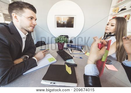 three young people in office suits are actively discussing something sitting at the table