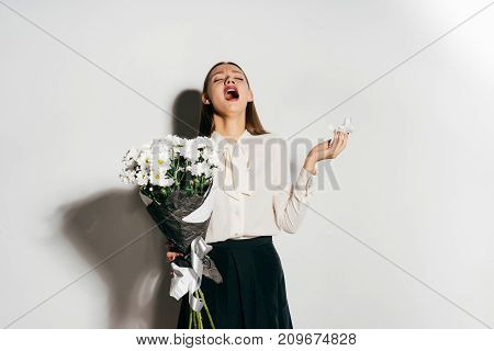 young happy lovely girl holding a large bouquet of white flowers in hands and sneezing because she is allergic