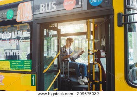 Asian Male Tourist Sitting In City Bus And Reading A Map.