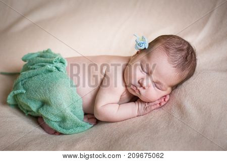 Sleeping newborn baby girl in a green knit panties. Sleeping on a covered sheet.