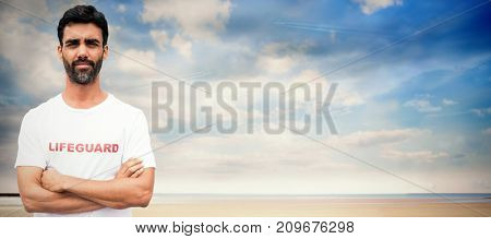 Portrait of male lifeguard with arms crossed against serene beach landscape