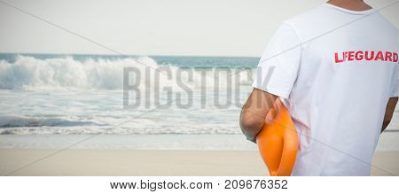 Mid section of male lifeguard with rescue buoy against two starfish kept on sand