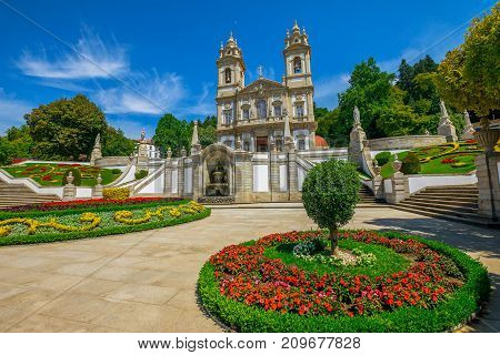 Neoclassical Basilica of Bom Jesus do Monte surrounded by bloom gardens in a sunny day with blue sky. Popular landmark and pilgrimage site in north of Portugal. Tenoes in Braga city.