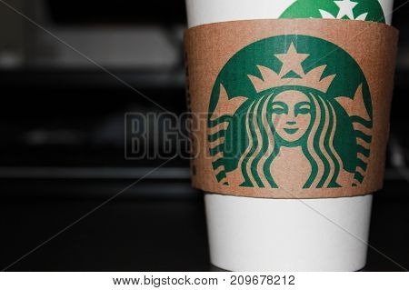 MOSCOW, RUSSIA - OCTOBER 9, 2017: Starbucks Coffee To Go paper Cup on Black Table at the Office Background. Take away drink in white cup with Starbucks logo in front of the computer at workplace.