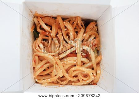 Noodles Udon Pasta Made in Wok with Chicken, Vegetables and Sesame in Take Away Box Top View. Typical Asian food cooked worldwide in white delivery paper box. Healthy organic meal option at home.