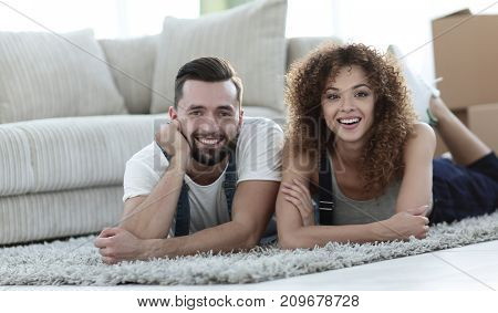 Happy couple lies on the floor in a new apartment