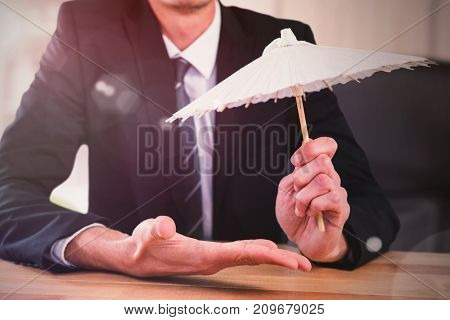 Composite image of businessman holding paper umbrella