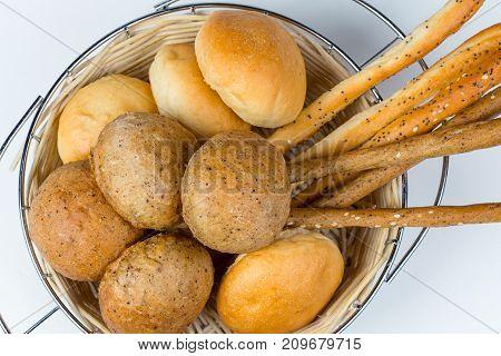 Bread assortment in wicker basket on white background