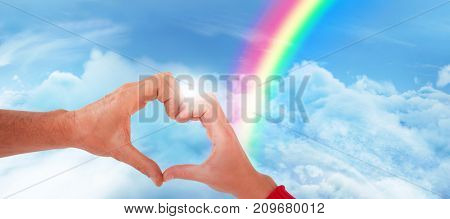 Couple making heart shape with hands against idyllic view of cloudscape against sky