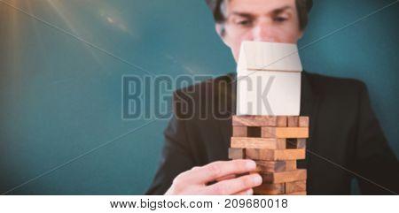 Businessman arranging wooden blocks at table against blue