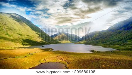 Idyllic view of lake and mountains against sky