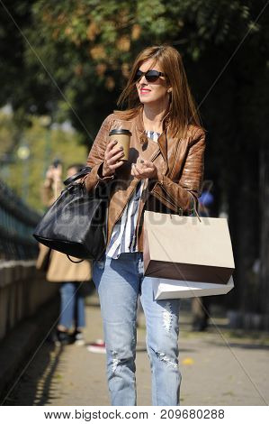 Fashionable, nice and attractive young woman is shopping in the city with paper bags in her hand. City style conception.