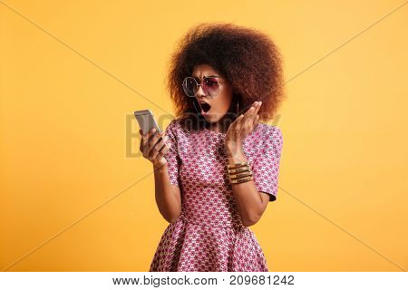 Portrait of a shocked surprised afro american woman in retro style clothes yelling at mobile phone while standing isolated over yellow background