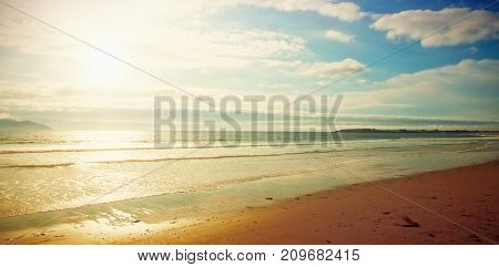 Idyllic view of seascape against cloudy sky during sunset