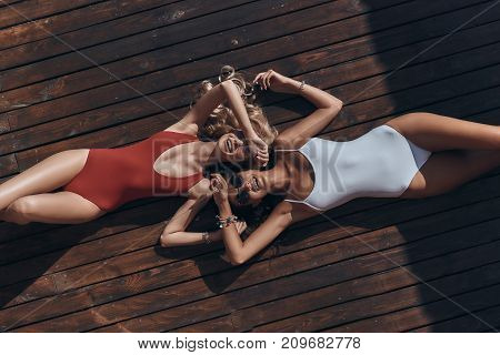 Enjoying summer. Top view of two attractive young women in swimwear smiling while lying down outdoors poster