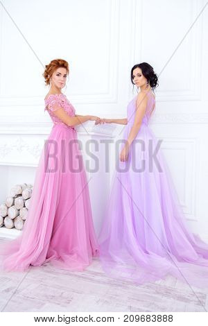 Two beautiful ladies in elegant evening dresses stand in white luxurious apartments. Beauty, fashion. Wedding style.