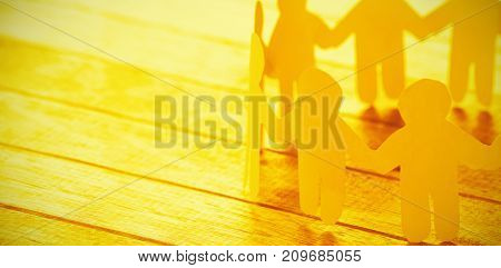 High angle view of yellow paper figures holding hands on wooden table