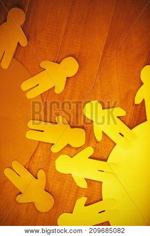 Overhead view of blue and yellow paper cut out figures on wooden table