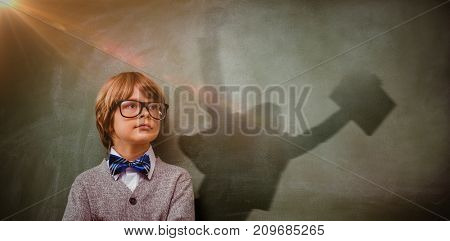 Businessman jumping while holding briefcase against boy with arms crossed looking up at blackboard