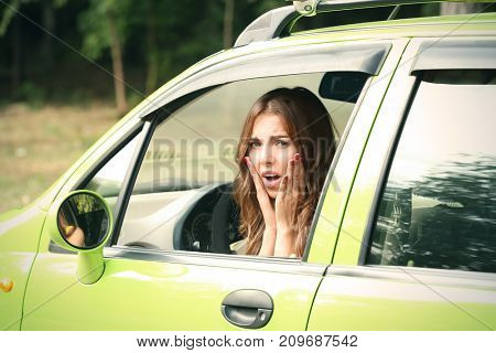 Upset young woman in car