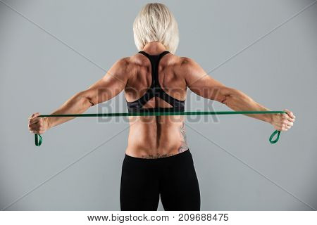 Back view portrait of a strong muscular adult sportswoman working out with a stretching band isolated over gray background