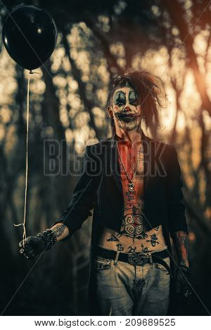 Portrait of a scary punk clown man smeared with blood in a night forest. Halloween. Horror, thriller film.
