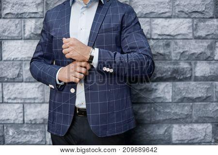 Handsome successful businessman near brick wall