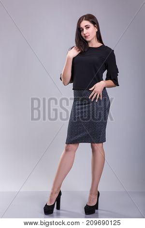 Full length portrait of a serious trendy brunette woman in black dress standing on a gray background