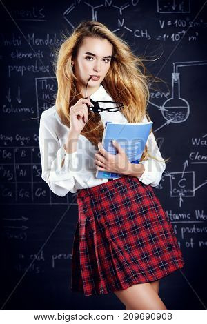 Cute student girl with long blonde hair posing in school uniform and glasses over blackboard background.
