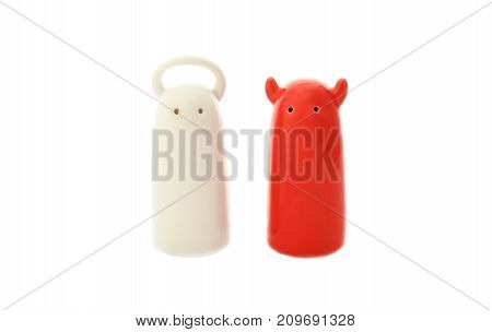 ceramic salt and pepper shakers in form of angel and demon on a white background.concept of cooking