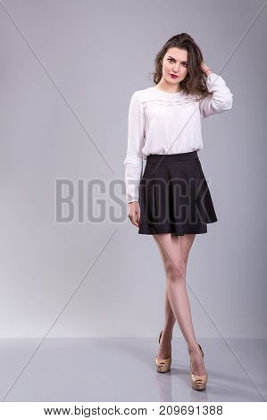 Full body portrait of young woman. Dressed in white blouse and black skirt beautiful woman stands over Gray background.