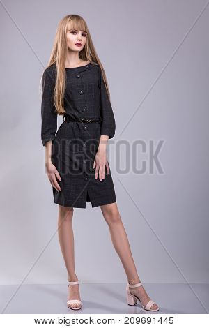 sexy woman with blond hair wear in black dress over grey background. studio shoot