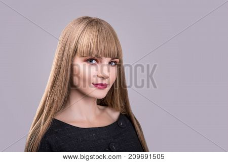 portrait of blonde beautiful fashion girl with bang over gray background