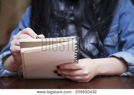 Young attractive business woman with long curly hair holds a job interview. Young beautiful woman journalist takes a journalist interviews. (Success news job concept).