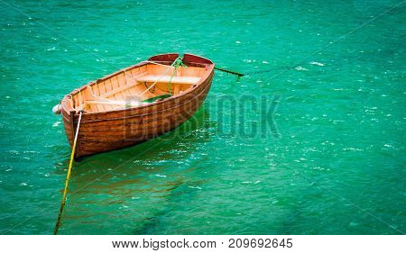 Boat moored on turquoise sea. Wooden boat moored and floating peacefully on clear water in the harbour