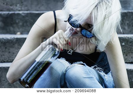 Young female with alcoholic drink looking very sad and depressed. Alcoholism in young adults (alcoholism pain pity hopelessness social problem of dependence concept)