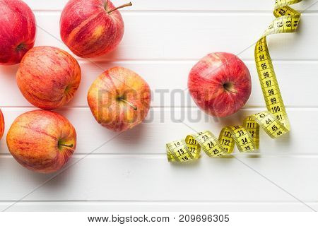 Red apple and measuring tape. Diet concept.