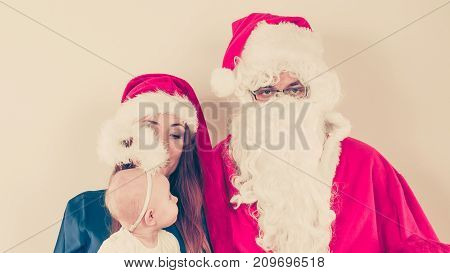 Christmas holiday concept. Man wearing Santa Claus costume with woman in christmassy hat.