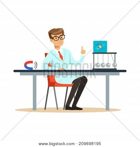 Young physicist sitting behind the desk with hand up. Atom symbol, newton s cradle, magnet. Man at workplace. Smart person cartoon character in lab coat. Flat vector illustration isolated on white.