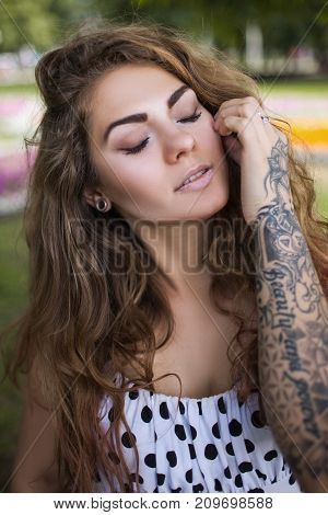 Modern female beauty closeup. Youth style. Relaxed woman portrait, pleasure feeling. Beautiful stylish girl with tattoo, fashion concept