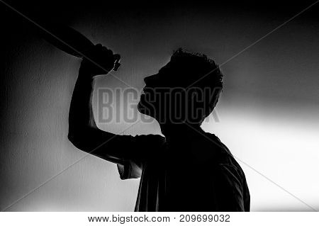 silhouette of an alcoholic on a white background with a empty bottle with a headache the next morning wants to get drunk stop alcoholism