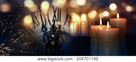 Burning candles with a clock and golden bokeh at turn of the year
