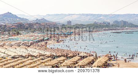 Sunny day atr beach of Pescara. Huge beach full of people and parasols Abruzzo Italy