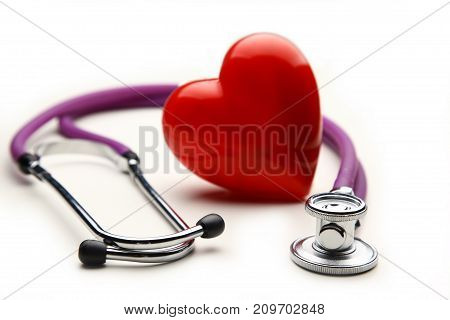 A heart with a medical stethoscope, isolated on wooden background