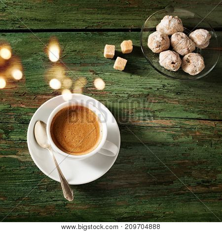 Espresso coffee with brown sugar and sweet pastry on shabby wooden table and bokeh
