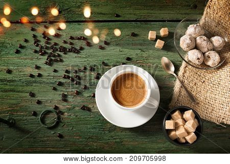 Espresso coffee with brown sugar and fresh coffee beans on shabby wooden table