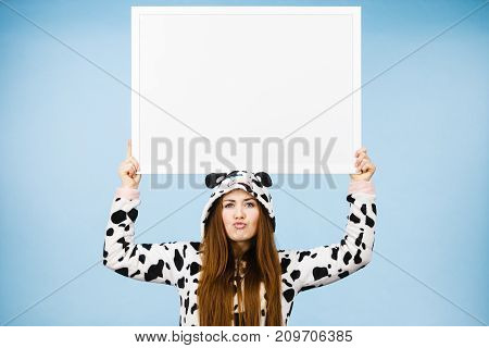 Positive teenage girl in funny nightclothes pajamas cartoon style with blank empty banner board. Advertisement copyspace.